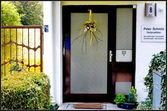 Praxiseingang zur Naturheilpraxis Schmitz Eingang Prxisschild von Heilpraktiker Peter Schmitz Haustüre Blumenarrangement Hecke Türgesteck Türschmuck Hausnummer 8 Gartentüre Fussabstreifer